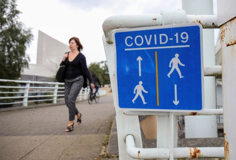 A woman walks past a social distancing sign, as the city with its surroundings face restrictions in an effort to avoid a local lockdown being forced upon the region to curb the spread of the coronavirus disease (COVID-19), in Manchester, Britain on August 4. (REUTERS Photo)