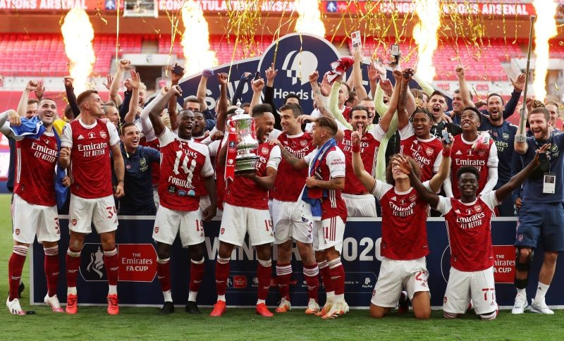 Arsenal's Pierre-Emerick Aubameyang celebrates with the trophy and teammates after winning the FA Cup, as play resumes behind closed doors following the outbreak of the coronavirus disease (COVID-19) Pool via REUTERS/Catherine Ivill