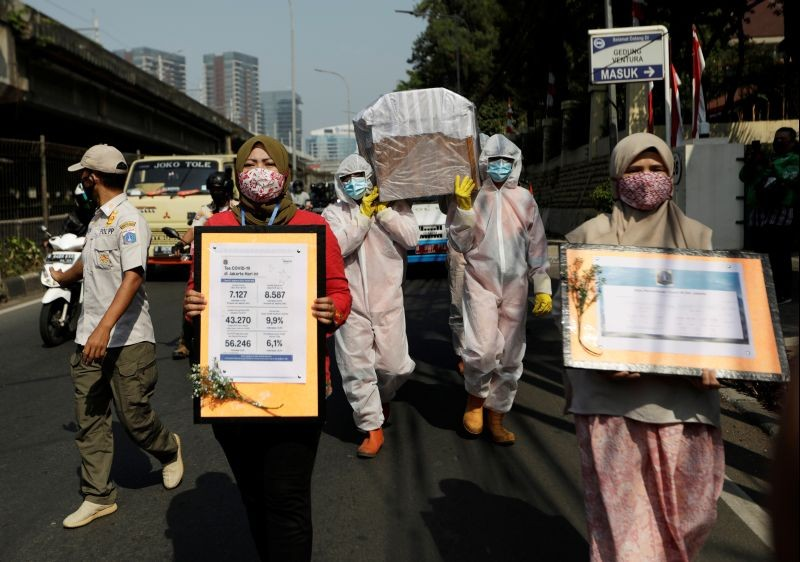Government workers wearing protective suits carry a mock-up of a coffin of a coronavirus disease (COVID-19) victim as others carry signs displaying information about the number of COVID-19 cases on a main road to warn people about the dangers of the disease as the outbreak continues in Jakarta, Indonesia on August 28, 2020. (REUTERS File photo)