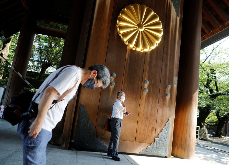 A visitor wearing a protective face mask bows his heads toward the main shrine as he visits to pay tribute to the war dead at Yasukuni Shrine ahead of the anniversary of Japan's surrender in World War Two, amid the coronavirus disease (COVID-19) pandemic, in Tokyo, Japan on August 14, 2020. (REUTERS Photo)