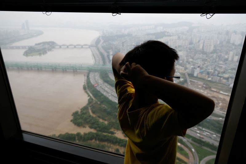 A boy looks down a flooded Han River park at an observatory platform in Seoul, South Korea on August 4. (REUTERS Photo)