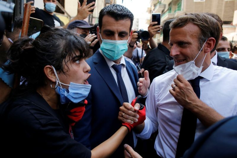 French President Emmanuel Macron listens to a resident as he visits a devastated street of Beirut, Lebanon on August 6. (REUTERS Photo)
