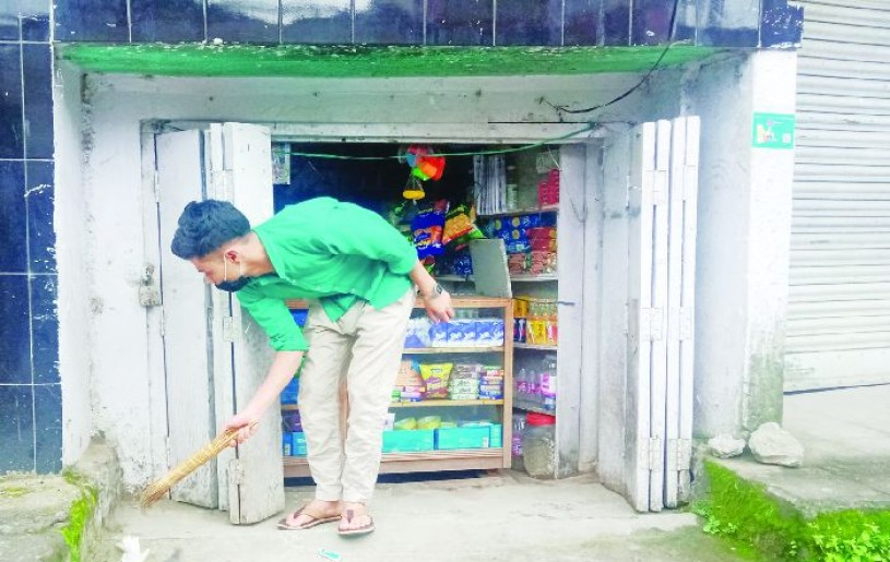 A salesman sweeps outside his shop to resume activities after the two week long total lockdown was lifted in Kohima on Saturday. (Morung Photo)