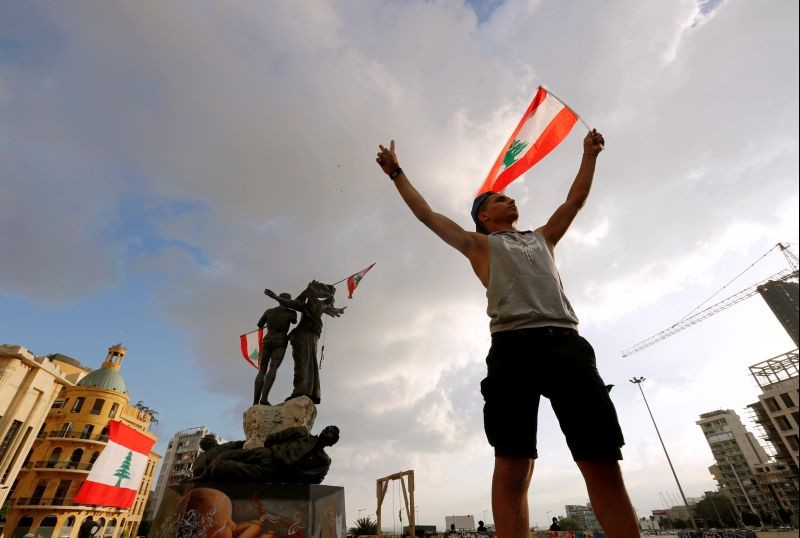 A demonstrator holds the Lebanese flag in Martyrs' Square where protests are held following Tuesday's blast in Beirut, Lebanon on August 9. (REUTERS Photo)