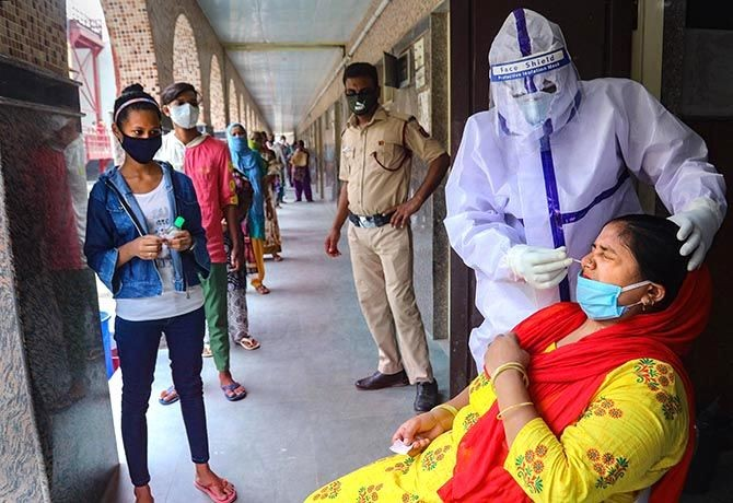 A medic collects samples from a woman in New Delhi.  PTI Photo