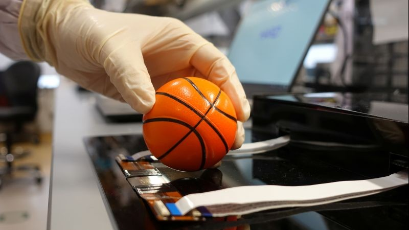 Dr. Benjamin Tee, Assistant Professor of Materials Science and Engineering at the National University of Singapore (NUS), demonstrates how his device can detect the texture of a soft stress ball at a lab in NUS, Singapore on July 27, 2020. (REUTERS File Photo)