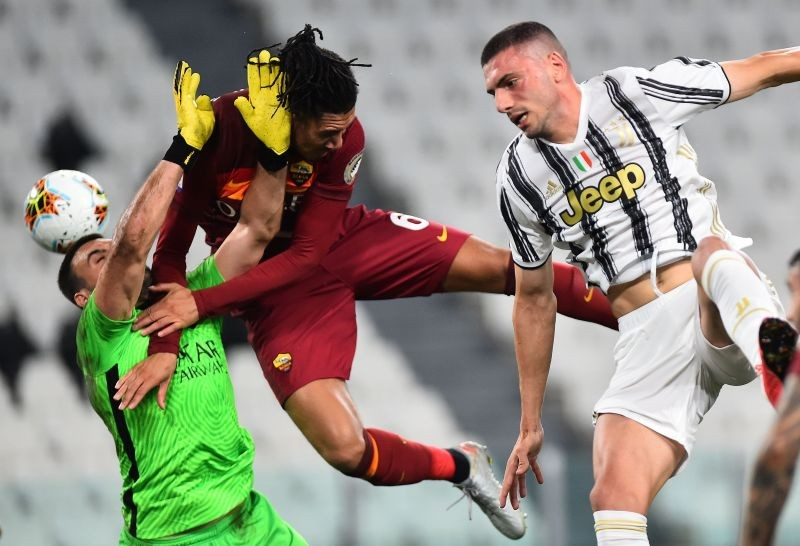 AS Roma's Chris Smalling and Daniel Fuzato in action with Juventus' Merih Demiral, as play resumes behind closed doors following the outbreak of the coronavirus disease (COVID-19) REUTERS/Massimo Pinca