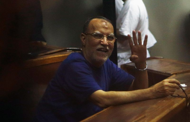 Deputy head of the Freedom and Justice Party Essam El-Erian waves with the Rabaa sign, symbolizing the support of the Muslim Brotherhood, during his trial with other leaders of the Muslim Brotherhood on charges of spying and terrorism at a court in the police academy on the outskirts of Cairo on November 18, 2014.  (REUTERS File Photo)