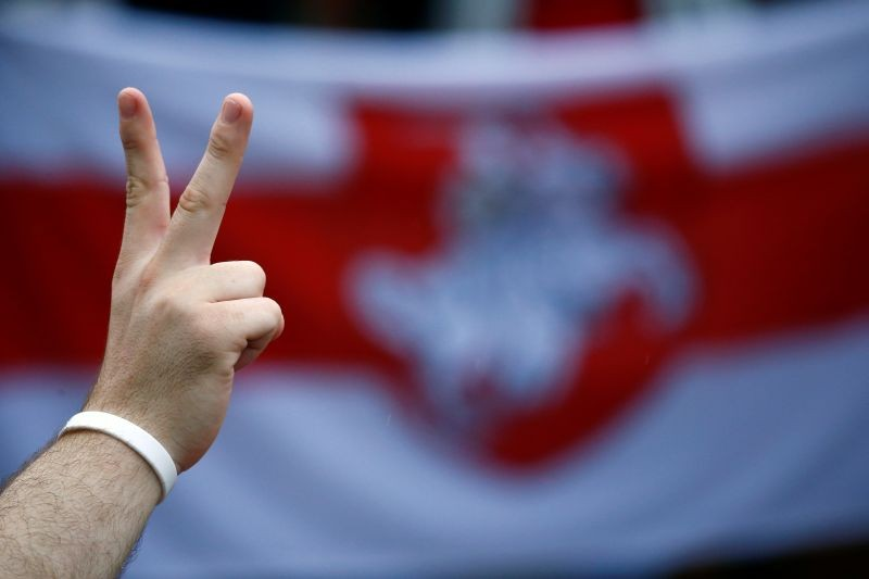 A person flashes the victory sign in front of a historical white-red-white flag of Belarus while attending an opposition demonstration to protest against presidential election results at the Independence Square in Minsk, Belarus on August 25, 2020. (REUTERS Photo)