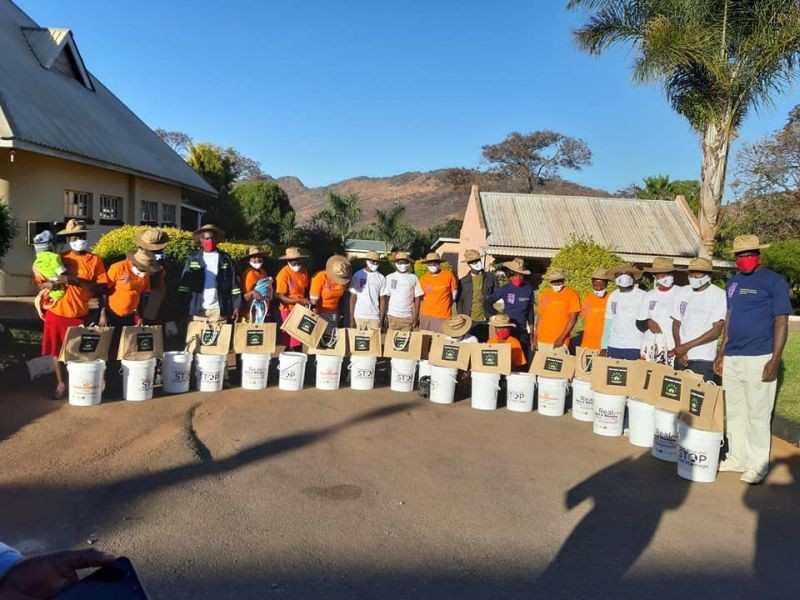 Roots Africa volunteers stand for a photo with buckets used to promote hand washing in Bindura, Zimbabwe on 20 July 2020. (Thomson Reuters Foundation File Photo)