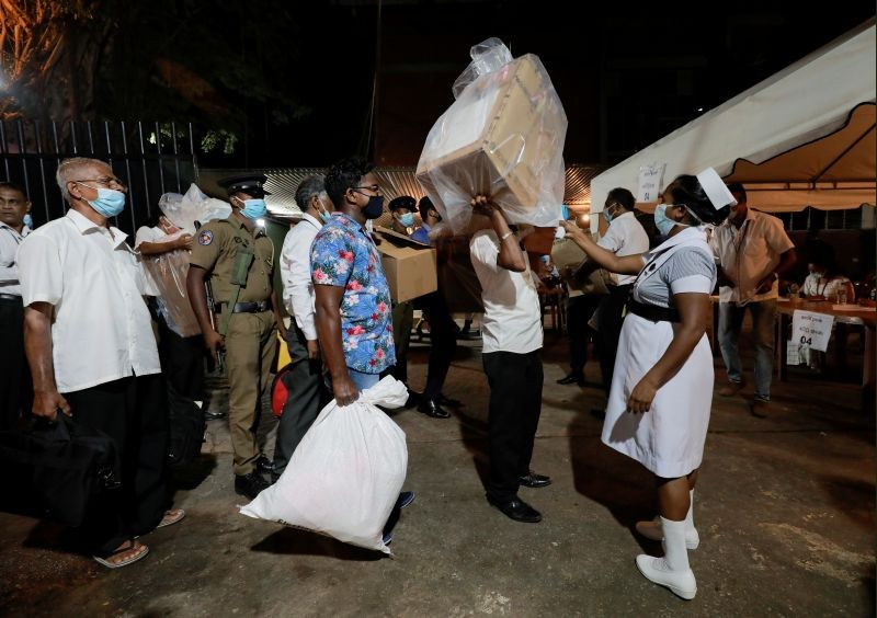 A health official takes the temperature of election officials who arrive with ballot boxes from a polling station to a counting center, after the voting ended during the country's parliamentary election in Colombo, Sri Lanka on August 5, 2020. (REUTERS Photo)