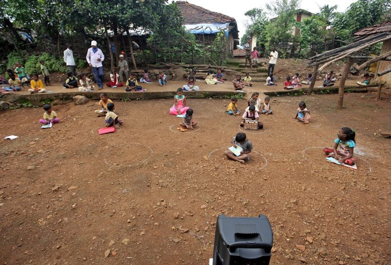 Children, who have missed their online classes due to a lack of internet facilities, sit on the ground in circles drawn with chalk to maintain safe distance as they listen to pre-recorded lessons over loudspeakers, after schools were closed following the coronavirus disease (COVID-19) outbreak, in Dandwal village in the western state of Maharashtra on  July 23, 2020. (REUTERS  File Photo)