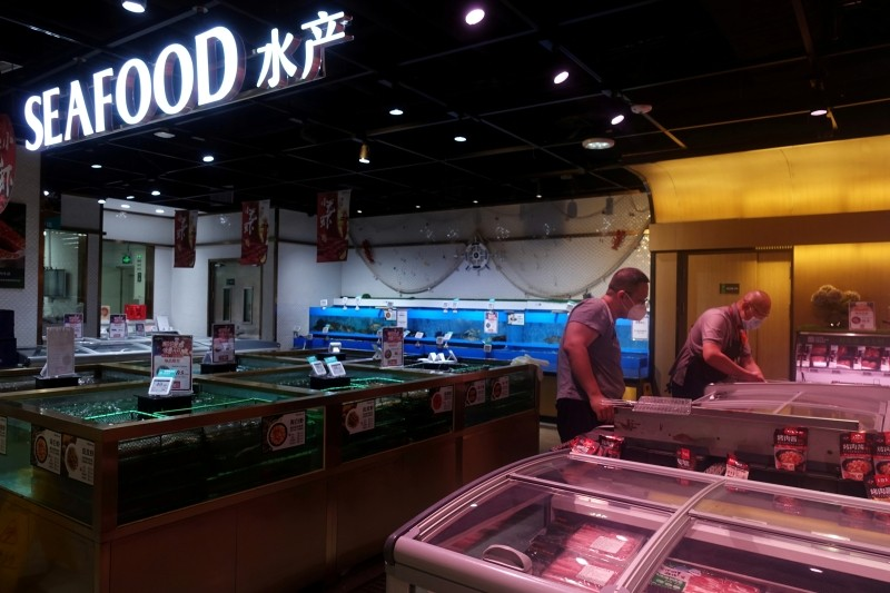 A staff member attends to a customer at a live seafood section inside a supermarket, following a new outbreak of the coronavirus disease (COVID-19), in Beijing, China June 20, 2020. (REUTERS File Photo)