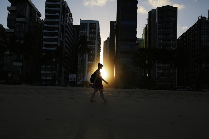 A woman walks on the beach as the sun sets between buildings in Recife on June 10, 2014.  (REUTERS File Photo)
