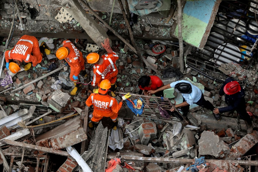 National Disaster Response Force (NDRF) officials and firemen remove debris as they look for survivors after a three-storey residential building collapsed in Bhiwandi on the outskirts of Mumbai, India, September 21, 2020. (REUTERS/Francis Mascarenhas)
