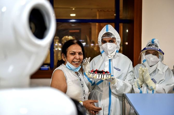 COVID-19 patient Renu Arora interacts with her family members via a robot as she celebrates her birthday with health workers inside a COVID-19 dedicated ward, at Yatharta Hospital in Greater Noida. Photograph: Arun Sharma/PTI Photo