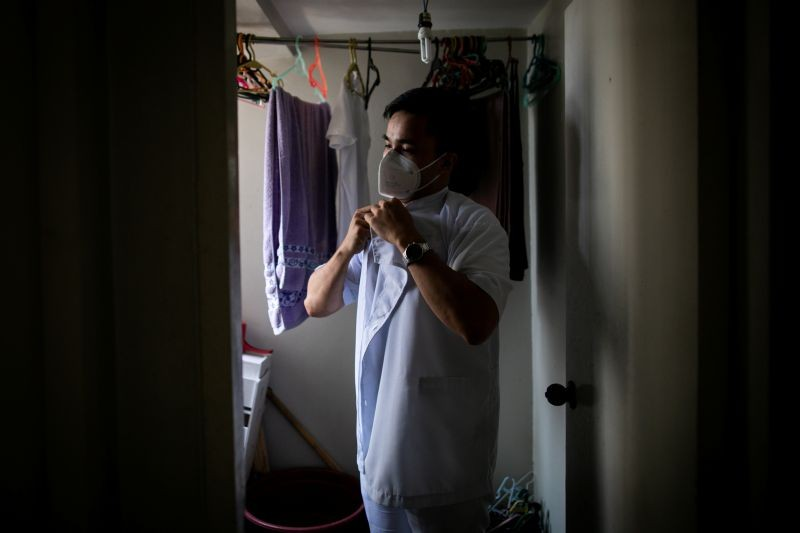 "Jordan Jugo, a nurse prevented from leaving the Philippines by a government restriction on health workers' movements, puts on his Philippine hospital work uniform at an apartment he shares with two roommates, in Mandaluyong City, Metro Manila, Philippines on September 4, 2020. ""It seems (the government) doesn't really value our contributions. It hurts"", he said. (REUTERS File Photo)"
