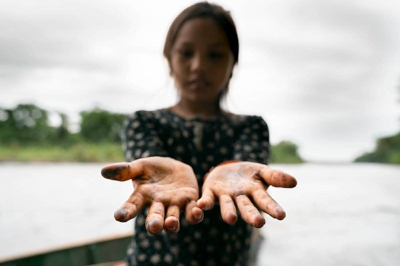 An indigenous girl's hands are stained from crude oil after playing along the riverbanks near the community of San Pedro de Río Coca, Sucumbios, northern Ecuadorian Amazon, April 18 2020. Telmo Ibarburu/Amazon Frontlines