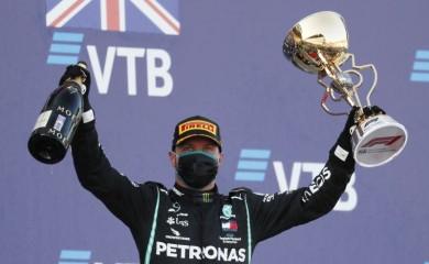 Mercedes' Valtteri Bottas celebrates with the trophy on the podium after winning the race. Pool via REUTERS/Yuri Kochetkov