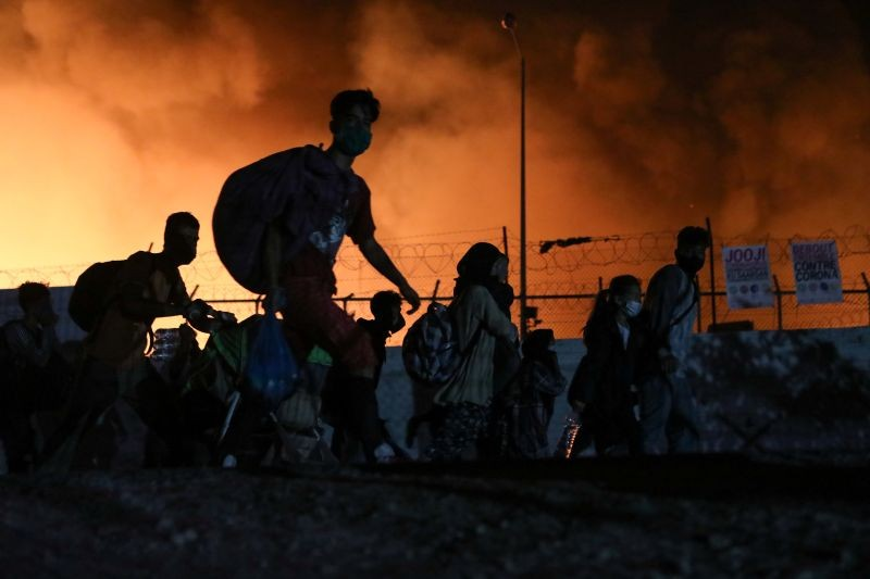 Refugees and migrants carry their belongings as they flee from a fire burning at the Moria camp, on the island of Lesbos, Greece on September 9, 2020. (REUTERS Photo)