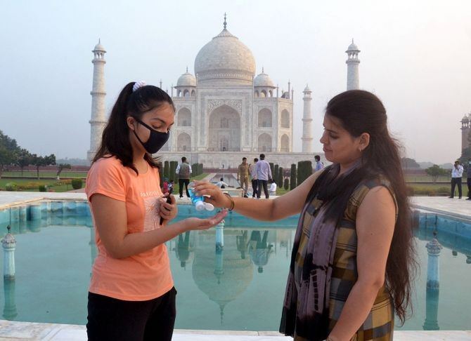 Two girls using hand sanitisers in front of the Taj Mahal after it reopens for the public as part of Unlock 4, in Agra on Monday. Photograph: Yatish Lavania/ANI Photo