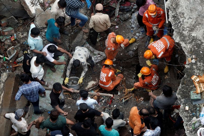 National Disaster Response Force (NDRF) officials search for survivors as people help clear the rubble after a three-storey building collapsed in Bhiwandi, on the outskirts of Mumbai, India, September, 21 2020. (REUTERS Photo)