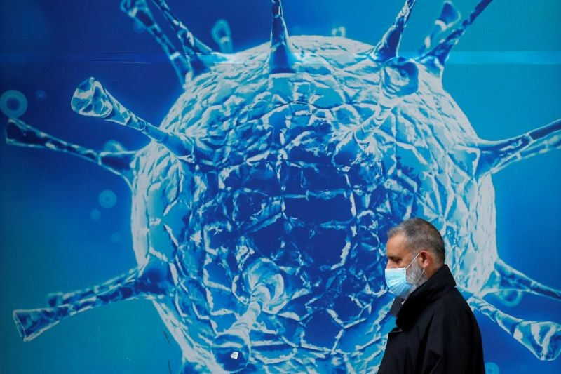 A man wearing a protective face mask walks past an illustration of a virus outside a regional science centre, as the city and surrounding areas face local restrictions in an effort to avoid a local lockdown being forced upon the region, amid the coronavirus disease (COVID-19) outbreak, in Oldham, Britain August 3, 2020. (REUTERS File Photo)