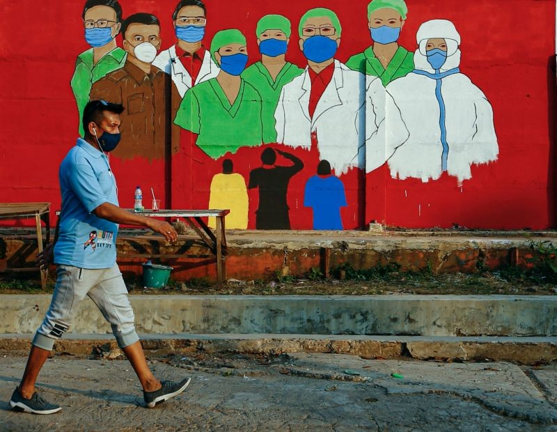 A man wearing a protective face mask passes a mural promoting awareness of the coronavirus disease (COVID-19) outbreak in Jakarta, Indonesia on August 31, 2020. (REUTERS File Photo)