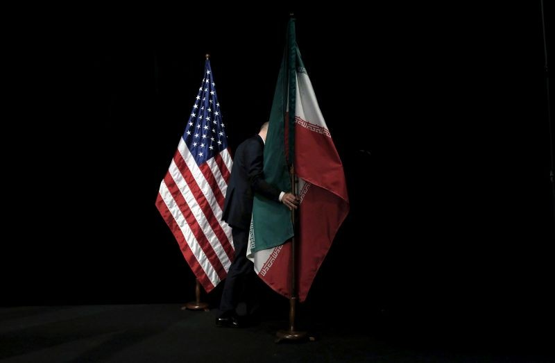 A staff member removes the Iranian flag from the stage after a group picture with foreign ministers and representatives of the U.S., Iran, China, Russia, Britain, Germany, France and the European Union during the Iran nuclear talks at the Vienna International Center in Vienna, Austria July 14, 2015. (REUTERS File Photo)