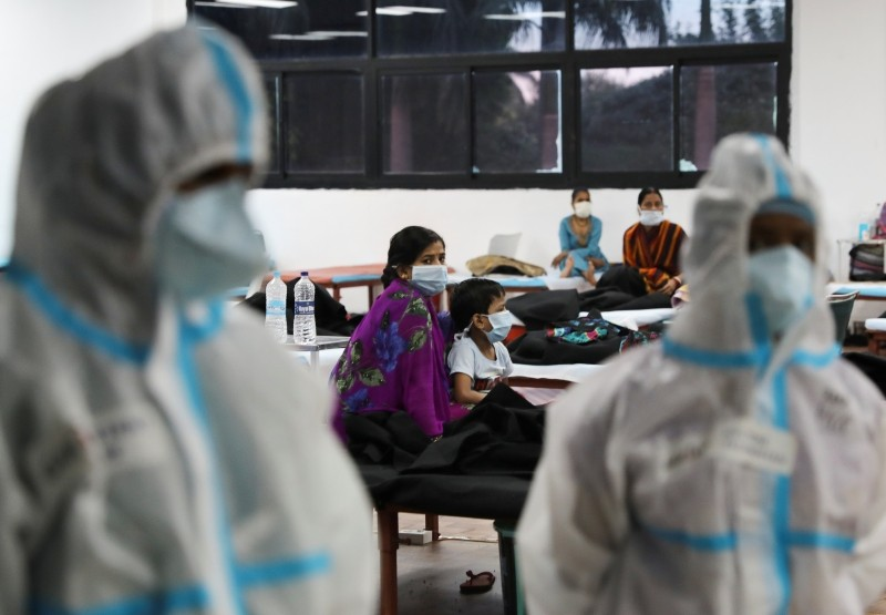 FILE PHOTO: A woman sits with her child inside a quarantine centre for the coronavirus disease (COVID-19) patients amidst the spread of the disease at an indoor sports complex in New Delhi, India, September 22, 2020. REUTERS/Anushree Fadnavis/File photo