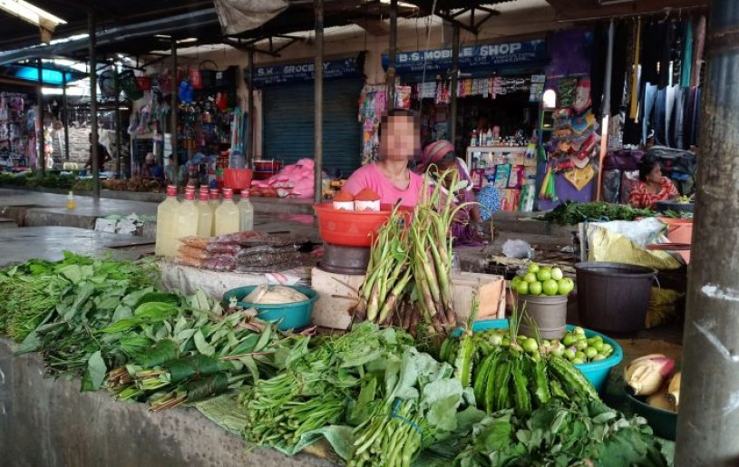 A woman vegetable vendor in Dimapur sits in a market  shed as she waits for customers. (Morung Photo: For representational purpose only.)