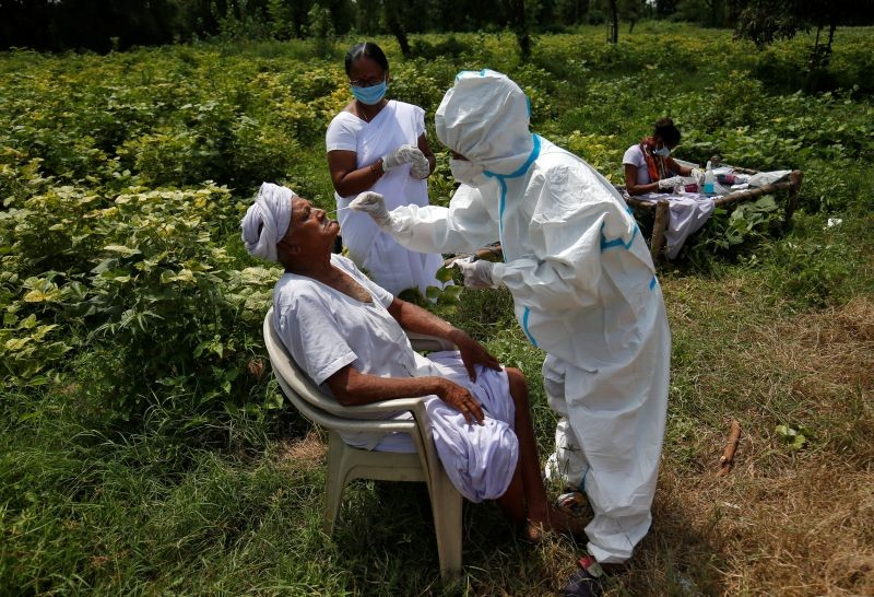 A healthcare worker wearing personal protective equipment (PPE) takes swabs from a farmer in a field, amidst the coronavirus disease (COVID-19) outbreak, in Kavitha village in Gujarat on September 15, 2020. (REUTERS Photo)