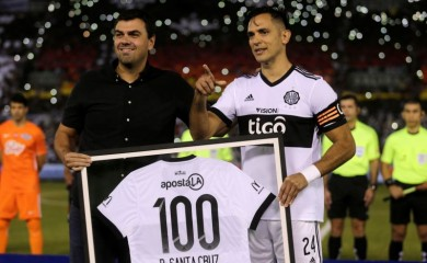Paraguay's Roque Santa Cruz (R) receives a prize from President of Olimpia Marcos Trovato for his 100th game before the match. REUTERS/Jorge Adorno/Files