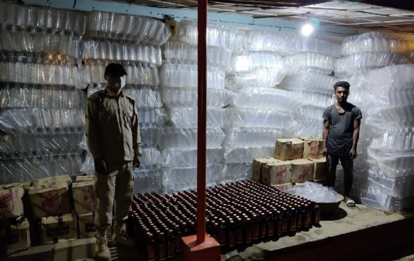 The arrested person along with the seized empty bottles and IMFL.