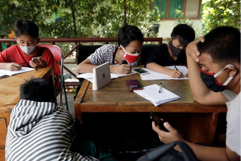 Dimas Anwar Saputra, a 15-year-old junior high school student, wearing a red protective mask, studies with other students using free internet wifi access that they got by exchanging plastic waste, amid the coronavirus disease (COVID-19) outbreak, at a local district office in Jakarta, Indonesia on September 9, 2020. (REUTERS Photo)