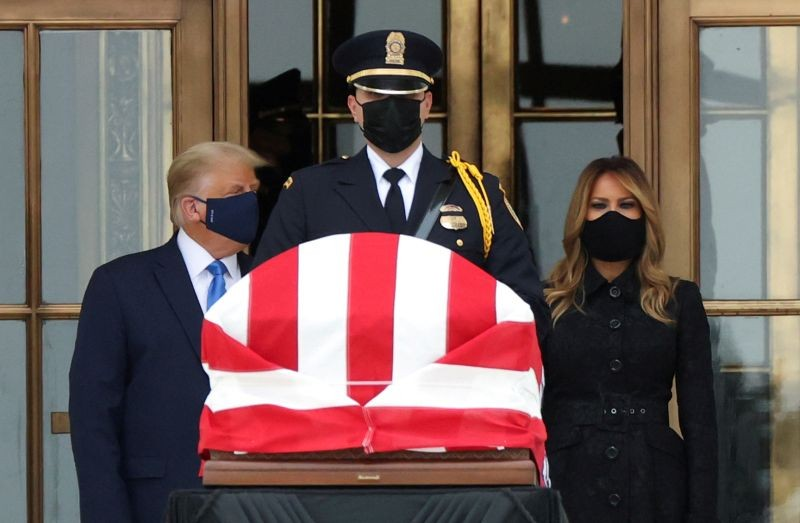 U.S. President Donald Trump reacts to people on the sidewalk booing him while he and First Lady Melania Trump pay their respects to late Associate Justice Ruth Bader Ginsburg as her casket lies in repose at the top of the steps of the U.S. Supreme Court building in Washington, US on September 24. (REUTERS Photo)