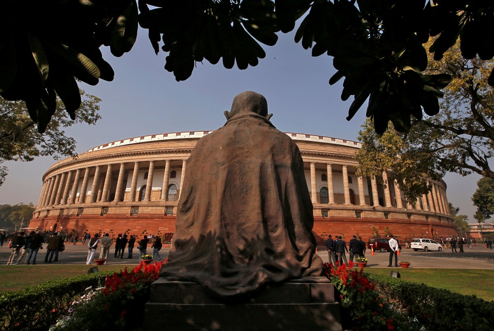 People stand in front of the parliament building in New Delhi, India, February 1, 2018. REUTERS/Adnan Abidi/Files