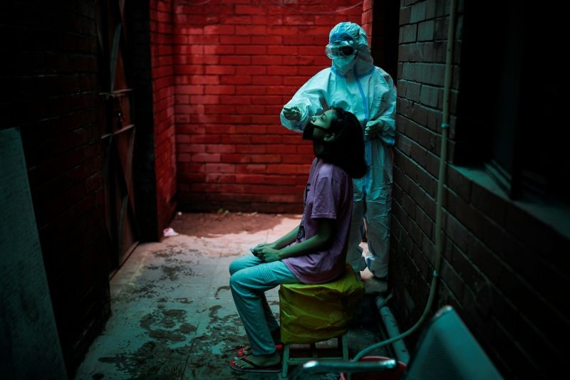 A health worker in personal protective equipment (PPE) collects a sample using a swab from a person at a local health centre to conduct tests for the coronavirus disease (COVID-19), amid the spread of the disease, in New Delhi on August 31, 2020. (REUTERS Photo)