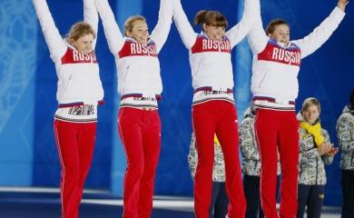 Silver medallists Russia's Yana Romanova, Olga Zaitseva, Ekaterina Shumilova and Olga Vilukhina (L-R) jump on the podium during the victory ceremony for the women's biathlon 4 x 6km event at the 2014 Sochi Winter Olympics February 22, 2014. REUTERS/Shamil Zhumatov/File Photo