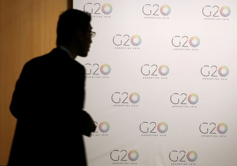A man stands next to a board with the G20 Meeting of Finance Ministers logo in Buenos Aires, Argentina, March 19, 2018. (REUTERS File Photo)