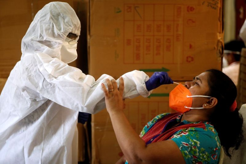 A health worker in personal protective equipment (PPE) collects a swab sample from a woman during a rapid antigen testing campaign for the coronavirus disease (COVID-19) in Mumbai on September 7, 2020. (REUTERS Photo)