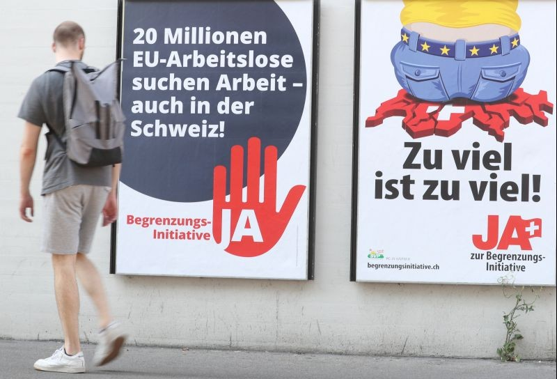 A man walks past posters of the Swiss People's Party (SVP) and of the Komitee Arbeitsplaetze fuer Einheimische schuetzen (committee to protect jobs for locals) against the anti-immigration initiative in Zurich, Switzerland on September 17, 2020. (REUTERS File Photo)