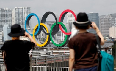 FILE PHOTO: Women look at the giant Olympic rings, which are being temporarily removed for maintenance, amid the coronavirus disease (COVID-19) outbreak, at the waterfront area at Odaiba Marine Park in Tokyo, Japan August 6, 2020. REUTERS/Kim Kyung-Hoon/File Photo