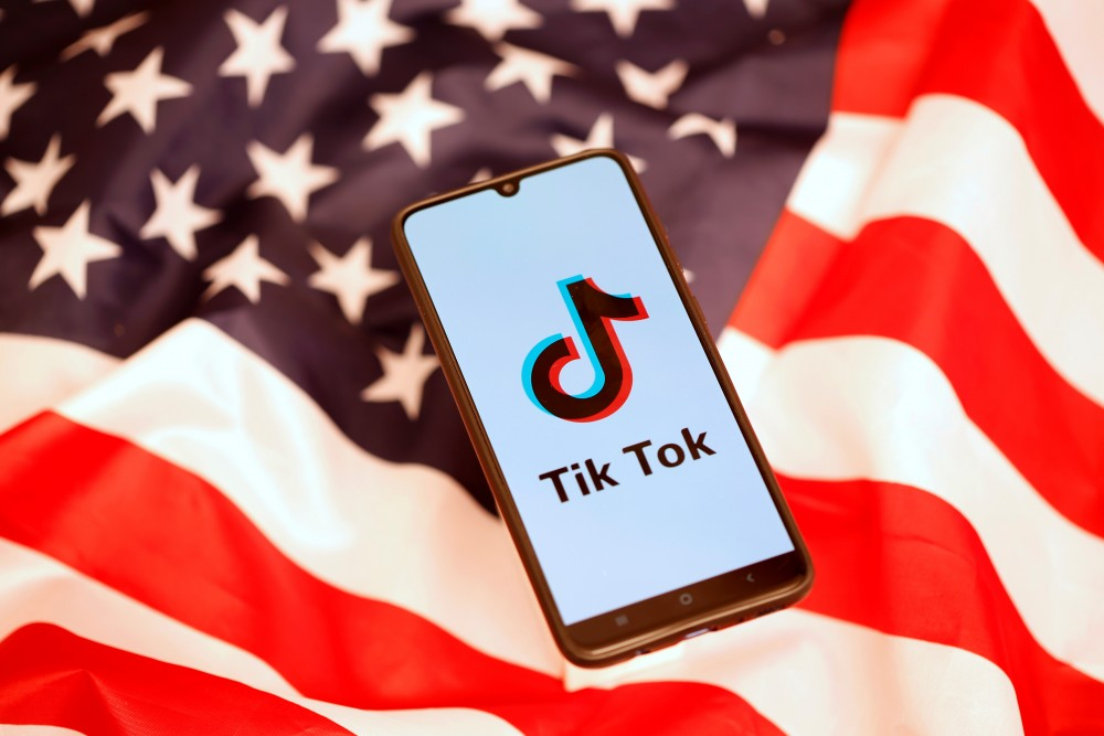 TikTok logo is displayed on the smartphone while standing on the U.S. flag in this illustration picture taken, November 8, 2019. REUTERS/Dado Ruvic/Files