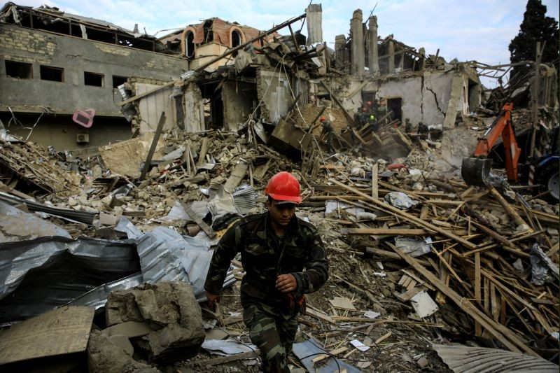 Search and rescue teams work on the blast site hit by a rocket during the fighting over the breakaway region of Nagorno-Karabakh in the city of Ganja, Azerbaijan October 11, 2020. (REUTERS Photo)