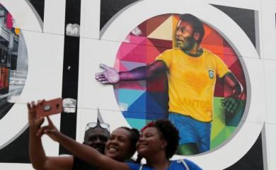 People take a selfie near a mural depicting Brazilian soccer legend Pele in Santos, Brazil October 20, 2020. REUTERS/Amanda Perobelli