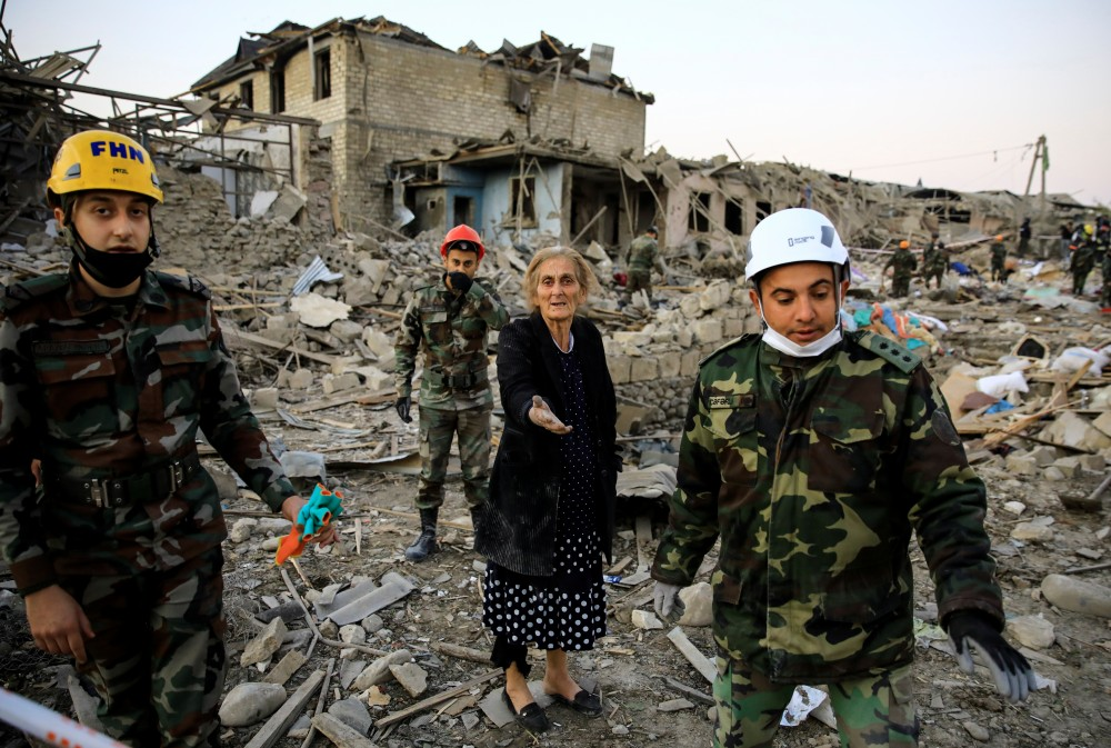 A woman reacts while standing on the ruins of her home as search and rescue teams work on a blast site hit by a rocket during the fighting over the breakaway region of Nagorno-Karabakh, in the city of Ganja, Azerbaijan October 17, 2020. REUTERS/Umit Bektas