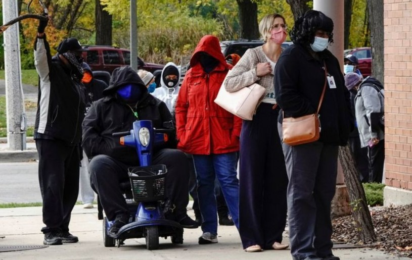 People wearing protective masks queue to enter a polling site at the Milwaukee Public Library?s Washington Park location in Milwaukee, on the first day of in-person voting in Wisconsin, U.S., October 20, 2020. REUTERS/Bing GuanREUTERS