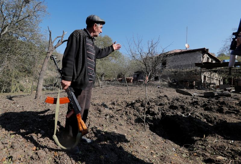 Local resident Alexei Agadzhanov holds a rifle while showing a crater following recent shelling in the settlement of Shosh in the course of a military conflict over the breakaway region of Nagorno-Karabakh, October 17, 2020. (REUTERS Photo)