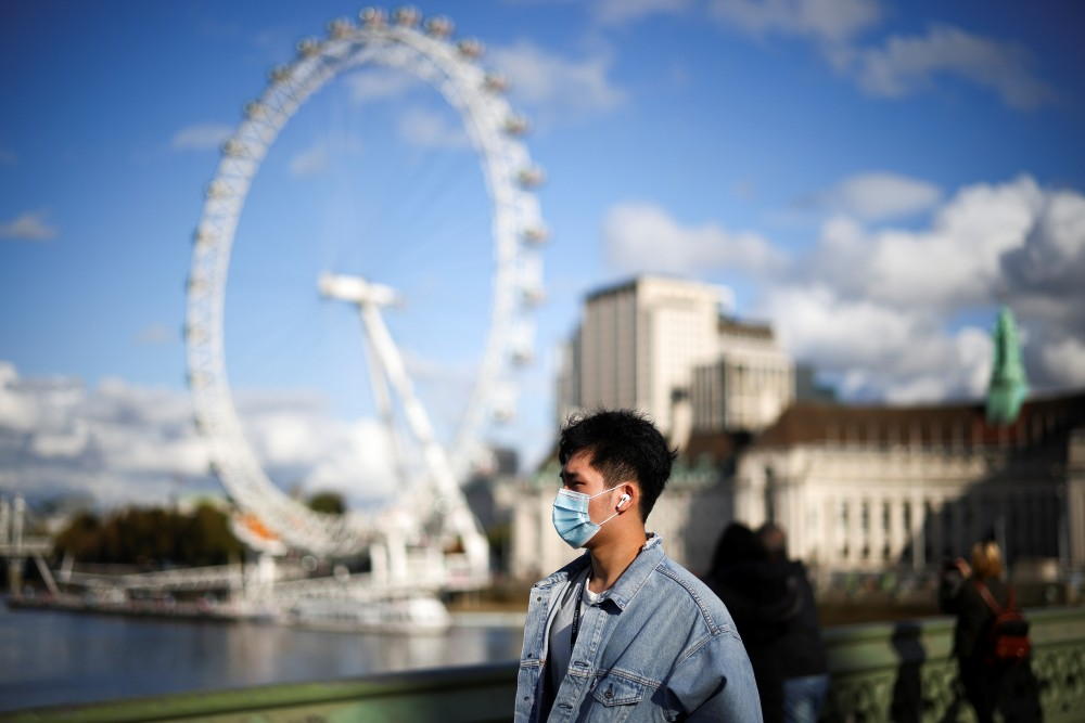 A man wearing a protective face mask walks across Westminster bridge, during the coronavirus disease (COVID-19) outbreak, in London, Britain, October 22, 2020. REUTERS/Henry Nicholls/Files